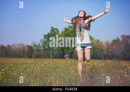 Happy and smiling hippie woman jumps in a summer field . Vintage photo effect - Stock Photo