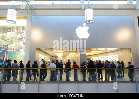 Shoppers queue outside the Apple store in Cardiff, South Wales, for the latest iPhone. - Stock Photo