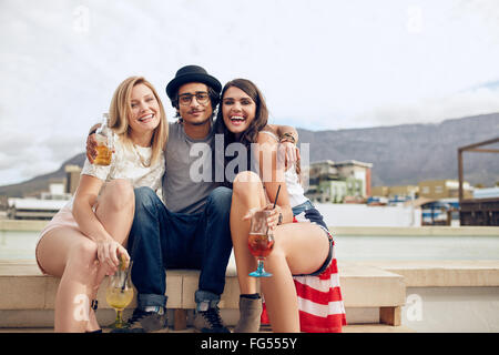 Portrait of best friends hanging out on a roof with drinks. Young man and women partying outdoors. - Stock Photo