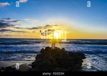 Woman With Sarong Blowing By Wind Standing On Rock In Sea Against Sky - Stock Photo