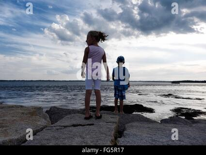 Rear View Of Siblings Standing On Rocks At Seaside Against Cloudy Sky - Stock Photo