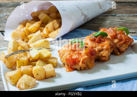 cod fish with tomato sauce and deep fried potato on tray - Stock Photo