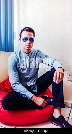 Young Man Wearing Sunglasses Sitting On Bean Bag Against Wall - Stock Photo