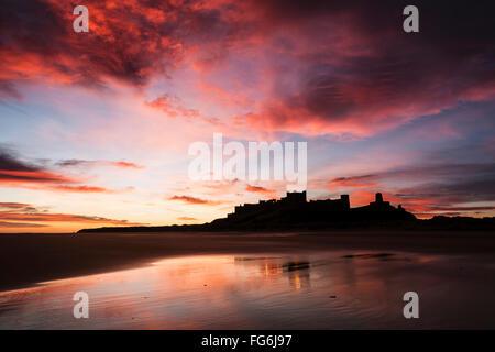 Bamburgh Castle viewed from Bamburgh Beach at sunrise, Bamburgh, Northumberland, England, United Kingdom - Stock Photo