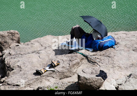 Elderly man is resting lying on a rock in the shade of his umbrella after trekking - Stock Photo