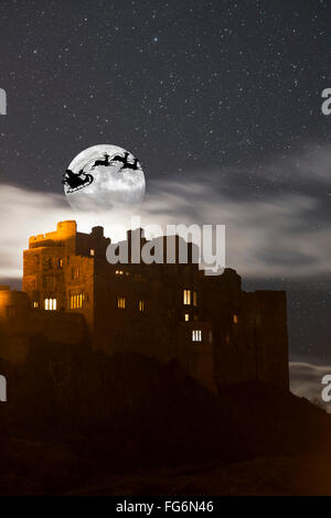Santa in his sleigh and reindeer silhouetted in the starry sky in front of the moon over buildings; Bamburgh, Northumberland, - Stock Photo