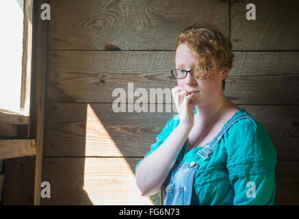 Portrait of a girl with curly red hair and eyeglasses standing against an old, wooden barn wall; Pittsboro, North - Stock Photo