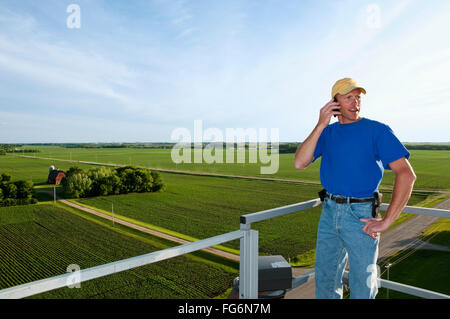 Agriculture - A young farmer talks on his cell phone atop a grain bin with a farmstead and fields in the background - Stock Photo