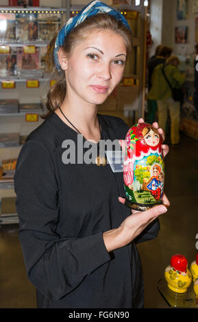 Young woman assistant holding a Matryoshka nesting doll in tourist store, Saint Petersburg, Northwestern Region, - Stock Photo