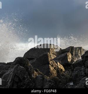 Water splashing in the air from waves crashing against the rocks; Tofino, British Columbia, Canada - Stock Photo