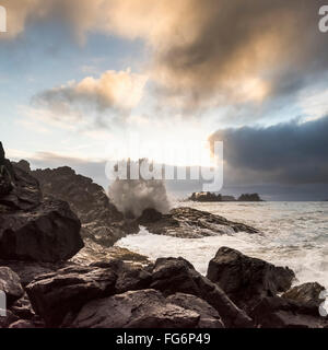 Glowing clouds at sunset with waves crashing against the rocks; Tofino, British Columbia, Canada - Stock Photo