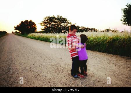 Brother And Sister Giving An Hug On The Road By Field - Stock Photo