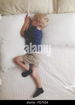 High Angle View Of Boy Sleeping On Bed - Stock Photo