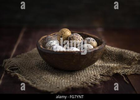 Fresh organic quail eggs in ceramic bowl on linen rag. Natural light, selective focus - Stock Photo