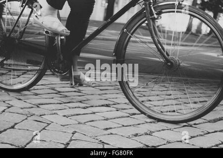 Low Section Of Man Cycling On Cobblestone Street - Stock Photo