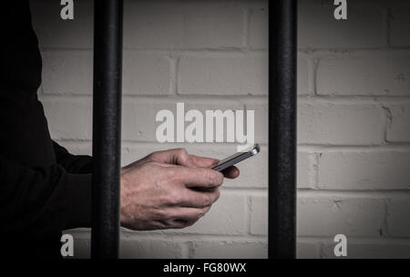 A prisoner in prison using a mobile phone behind bars in a cell - Stock Photo
