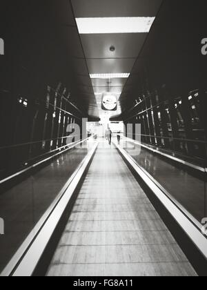 Rear View Of Man On Moving Walkway In Airport