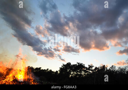 Low Angle View Of Bonfire By Silhouette Trees Against Sunset Sky During Easter - Stock Photo