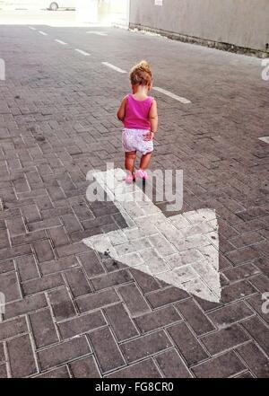 Rear View Of Girl Walking Over Arrow Symbol On Cobblestone Street - Stock Photo