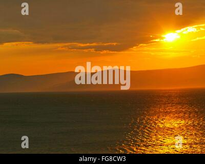 Idyllic View Of Sea And Mountains Against Cloudy Sky During Sunset - Stock Photo