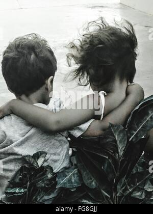 Rear View Of Siblings With Arm Around Outdoors - Stock Photo
