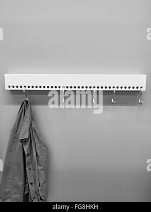 Shirt Hanging On Hook Against Wall In Room - Stock Photo