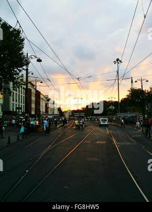 People By Railroad Tracks On City Street Against Sky During Sunset - Stock Photo