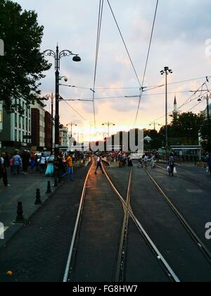 People On Railroad Tracks At City Street Against Sky - Stock Photo