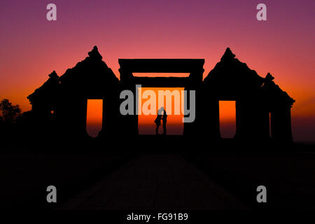 Silhouette Couple Kissing On Gateway Of Ratu Boko Ruins Against Clear Sky - Stock Photo