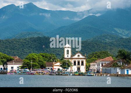 Tourist boats waiting for tourists near the Church Igreja de Santa Rita de Cassia in Paraty - Stock Photo