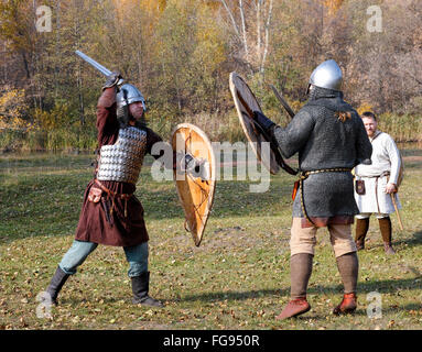 Two warriors in old Russian armors reconstructed medieval fight with swords and shields on the battlefield. - Stock Photo