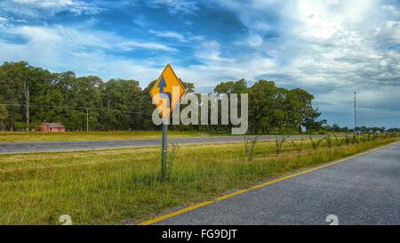 Arrow Sign By Road Against Cloudy Sky - Stock Photo
