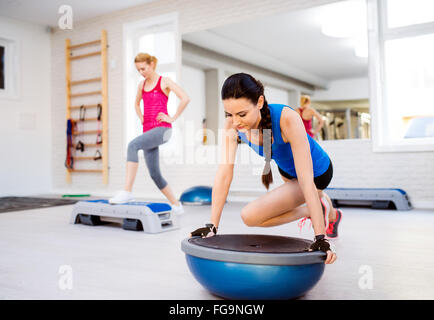 Two fit attractive women in gym doing various exercises - Stock Photo