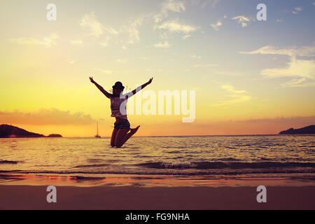 Beautiful energy young woman silhouette jumping on beautiful sunset bright background - Stock Photo