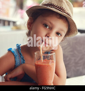 Fun cute kid girl drinking healthy smoothie juice in street restaurant. Closeup toned portrait - Stock Photo
