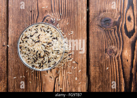 Uncooked Rice (mixed with wild Rice) on rustic background - Stock Photo