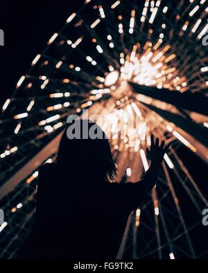Low Angle View Of Silhouette Girl Against Illuminated Ferris Wheel At Night In Amusement Park - Stock Photo