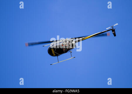 Robinson R22 G-OSAZ is a two-bladed single-engine light utility helicopter flying overhead near the airport in Dundee, - Stock Photo
