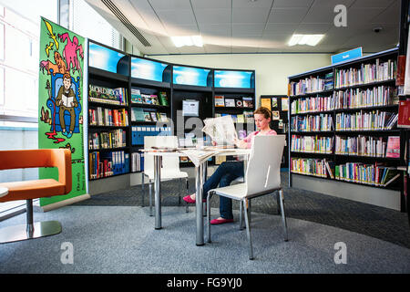 Young Girl sits and reads in  Library - Stock Photo