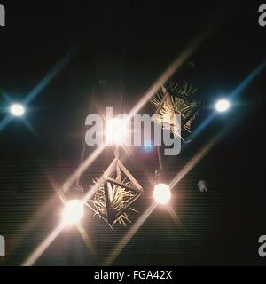 Low Angle View Of Illuminated Light Bulbs Hanging Against Wall - Stock Photo