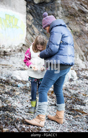 Middle-class white mum and young daughter on a beach in winter looking for shells, pebbles and Mermaid rings - Stock Photo