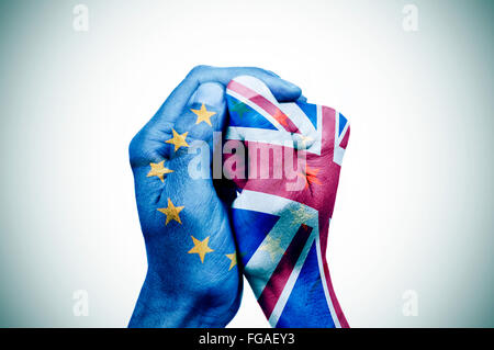 hand patterned with the flag of the European Community envelops another hand patterned with the flag of the United - Stock Photo