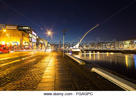 Illuminated Samuel Beckett Bridge Over River Against Sky - Stock Photo
