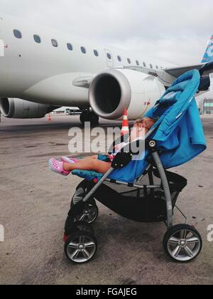 Baby Sleeping In Baby Carriage On Street Against Airplane - Stock Photo