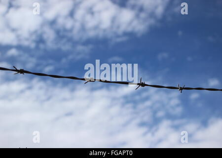 Low Angle View Of Barbed Wire Against Cloudy Sky - Stock Photo