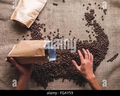 Cropped Hand Pouring Coffee Beans In Package - Stock Photo