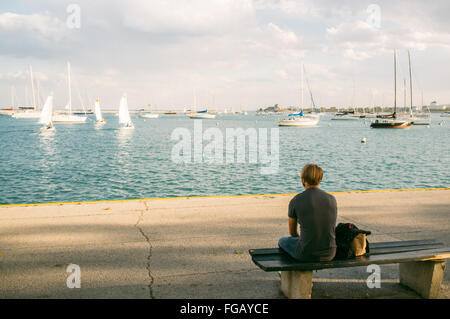 Rear View Of Man Sitting On Bench Overlooking Boats Sailing In Sea - Stock Photo