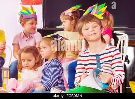 Boy with textbook in kindergarten class - Stock Photo