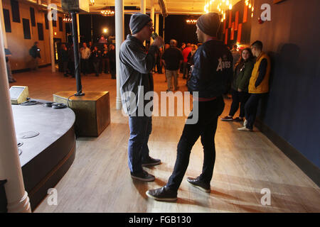 Iowa, USA. 17th Feb, 2016. Founder of Daytrotter Sean Moller, right talks with a festival goer before the music - Stock Photo