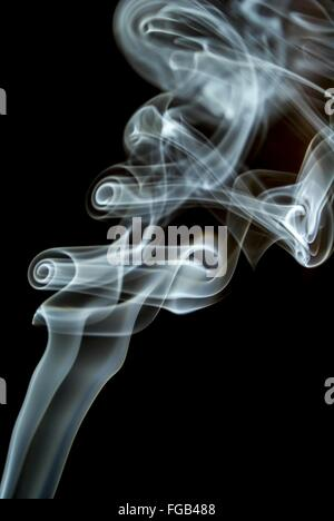 Close-Up Of Incense Smoke Against Black Background - Stock Photo